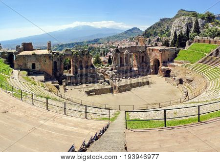 The famous and beautiful ancient greek theatre ruins Taormina with Etna volcano in the distance. outdoor shot Sicily Italy