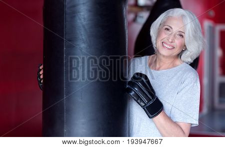 My favorite hobby. Portrait of pretty smiling senior lady standing at punchbag in fitness club.
