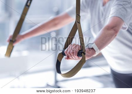 Intensive workout. Close-up of elderly woman doing exercises by leaning on special fitness equipment at gym.