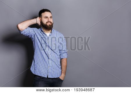 Handsome bearded man touching his hair. Young confident guy in relaxed pose, gray studio background. Flirt, seduction concept