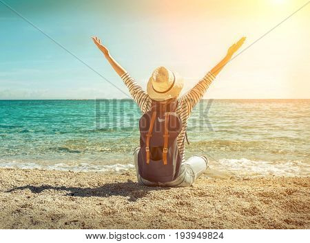 Blonde woman in summer hat with her backpack sitting on the sand by the sea beach. Sea view. Freedom. Wind. Summer. Beach. Vacation. Looking to a sky and sea. Looking forward