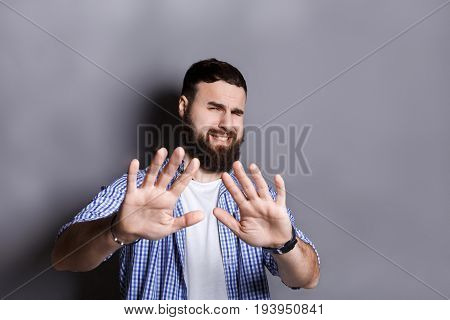Bearded pushing away with his hands in foreground, expressing his refusal, aversion or repulsion with stopping hand gesture, gray studio background
