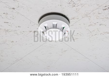 Smoke Detector Of Fire Alarm On White Ceiling At Home