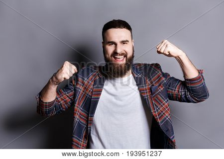 Excited bearded man very glad to success. Young cheerful guy in checkered jacket smiling at camera and gesturing with hands, gray studio background