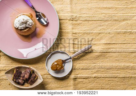 Flan - creme on top on a pink plate over a wooden board served with chocolate cookies dulce de leche confection coffee and nuts. poster