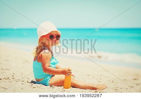 sun protection - little girl with suncream on tropical beach