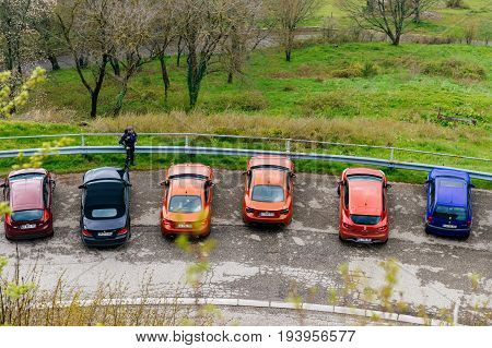Alsace France - May 1. 2016: Aerial View of cars parked in green parking. BMW REnault VW and two red The Toyota 86 a series of 2+2 seater sports cars which was jointly developed by Toyota and Subaru and solely manufactured by Subaru.
