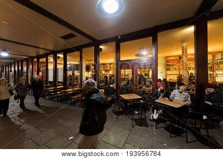 BRISTOL; UNITED KINGDOM - MAR 5; 2017: Exterior view of traditional England bar pub restaurant in the Harbourside at night full with people enjoying delicious food and drinking beer in the city of Bristol - view through street glass