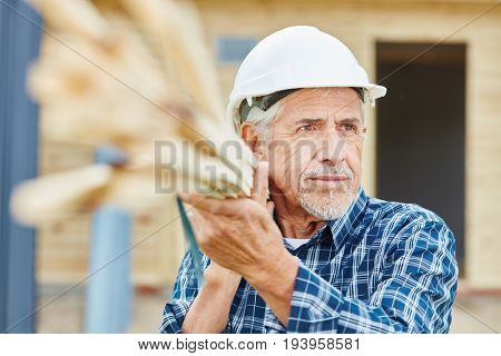 Senior craftsman working at construction site carrying wood
