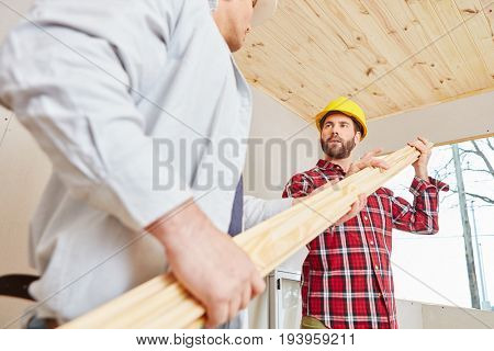 Two handymen working on woodhouse interior