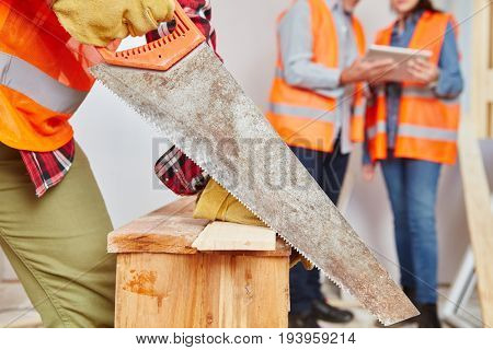 Craftsman with hand saw cutting wood at construction site