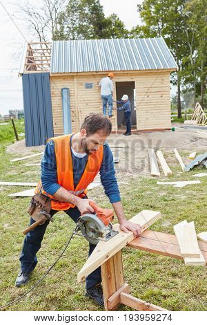 Craftsman working with circular saw at construction site
