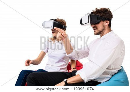 Excited young couple experiencing virtual reality seated on beanbags isolated on white background. A young couple, both in jeans and white T-shirts. VR