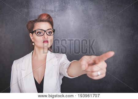 Serious Teacher Pointing Out On Chalkboard Background