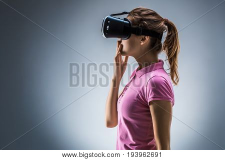 Young woman wearing virtual reality headset on a gray background. Studio shoot. Emotions. Side view. VR