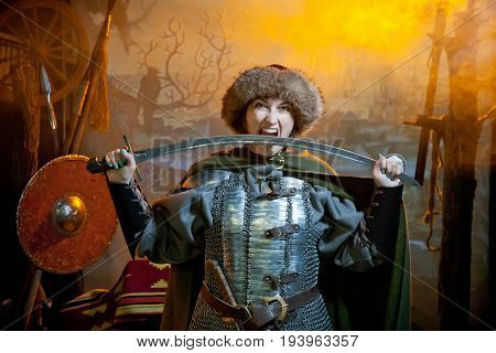 A woman biting scimitar dressed in chain mail cloak and fur hat against the background of weapons a branch with a crow and a castle in the distance