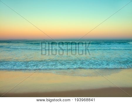 Retro styled instant camera style photo of a beach during sunrise dawn