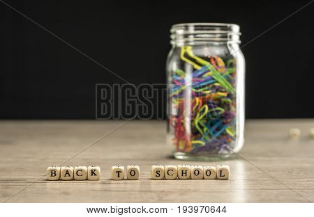 Back to school written in wooden blocks with a jar of paper clips