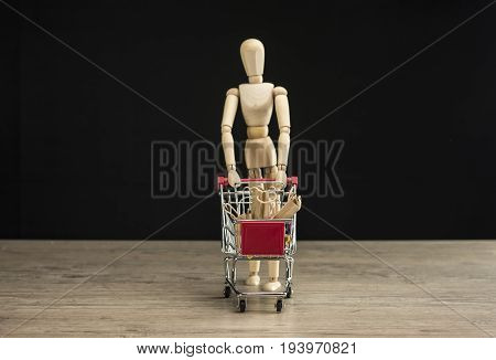 Wooden female human mannequin holding shopping trolley filled with shopping bags