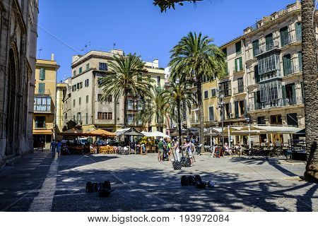 PALMA DE MALLORCA SPAIN - 11 JUNE 2017 - Diners eat in a pretty square in the sunshine in some of the many pavement cafes as a tourist group enjoy a segway tour