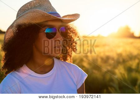 Beautiful happy mixed race African American female girl teenager young woman wearing reflective aviator sunglasses and cowboy hat in a cornfield at golden sunset or sunrise