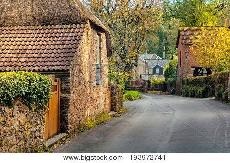 A quiet street with old houses in the village of Cockington. Autumn warm day. Foliage flies from trees. Devon. England
