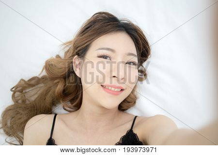 Beautiful young asian woman using smartphone for selfie on the bed 20s year old.