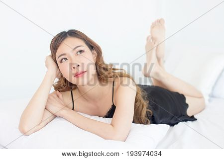 Beautiful young asian woman posing on the bed korean woman sexy concept 20s year old. poster