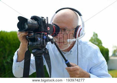 A mature man with headphones using a camera dslr