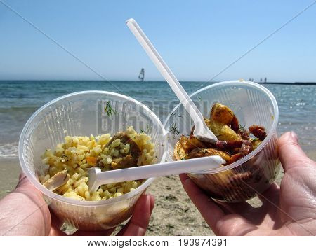Pilaf potato slices and sailboat on the horizon in the sea. Takeaway food to relax on the beach