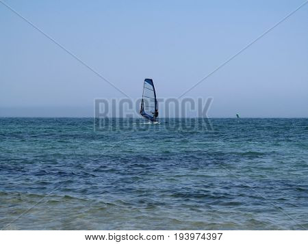 One windsurfer in the sea. Turquoise sea clear blue sky without clouds and a surfer with a blue sail in the middle photo