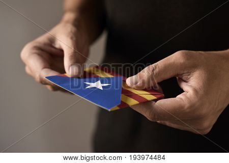 closeup of a young man with an envelope patterned with the Estelada, the Catalan pro-independence flag, depicting the Catalan independence referendum