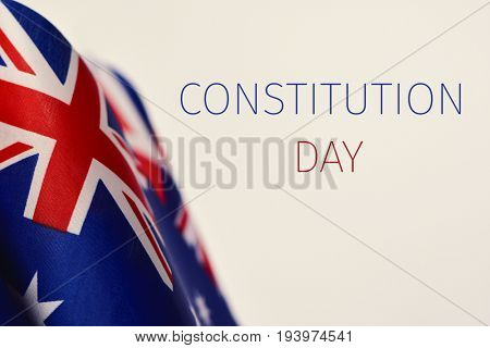 some Australian flags and the text Constitution Day written in blue and red against an off-white background