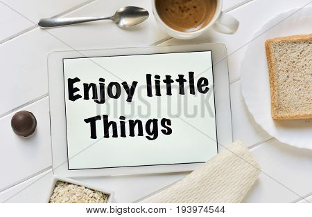 high-angle shot of a tablet with the text enjoy little things in its screen and a cup of coffee, a bowl with cereals and a plate with a slice of bread on a white table set for breakfast