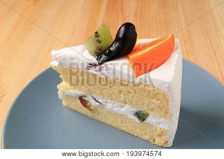 Vanilla Sponge Layer Cake Topped with Fruits Served on Blue Plate
