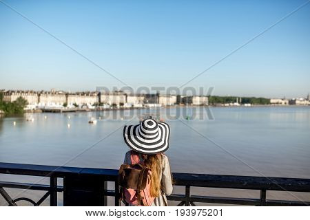 Young woman tourist enjoying great view on the city standing on the famous Pierre bridge in Boredaux city in France