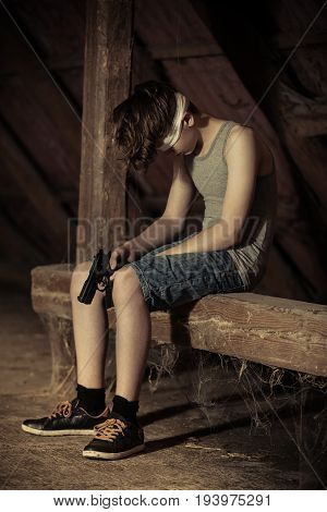 Sad Blindfolded Child Sitting With Pistol