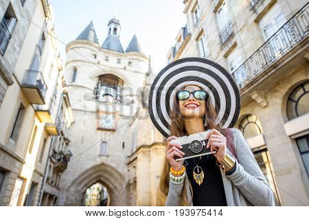 Young woman tourist with big hat and photo camera standing in front of the famous bell tower in Bordeaux city in France