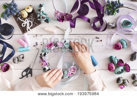 Handmade headbands making, home workshop. Unrecognizable woman artisan decorating hair hoop with flowers and ribbons, top view. Art, handicraft, creative concept