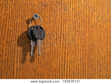 On the wooden wall of the Cabinet hang two keys.