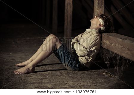 Barefoot teenage boy in captivity sitting on the floor in a dark rustic old wooden building in a blindfold and straight jacket poster