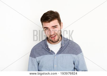 Cocky man grimacing, portrait. Portrait of young daring guy with sassy look, isolated on white background