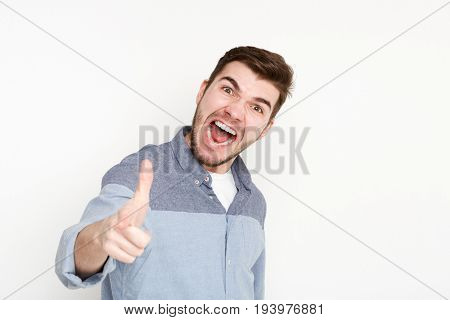 Furious man shouting loud and point at camera. Young angry guy screaming at you, isolated on white background