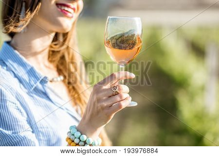 Young woman tasting wine standing outdoors on the vineyard in Bordeaux region during the sunset in France