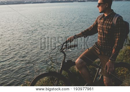 Young Man Standing With Bike On Coast And Enjoying View of Nature Sunset Vacation Traveling Relaxation Resting Concept