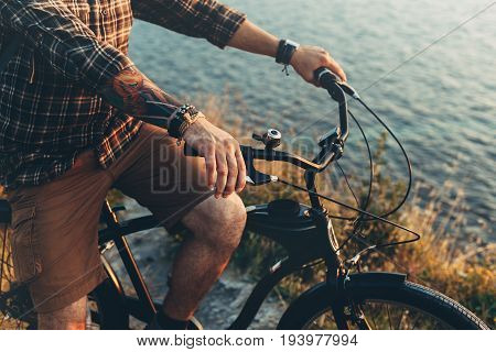 Unrecognizable Young Man Standing With Bike On Coast And Enjoying View of Nature Sunset Vacation Traveling Relaxation Resting Concept