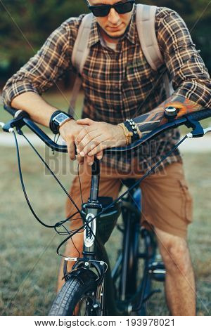 Young Man Cyclist In Sunglasses With Bicycle In Summer Park During Sunset Vacation Traveling Relaxation Resting Concept
