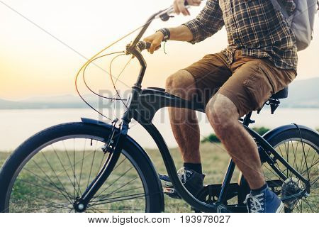 Unrecognizable Young Man Is Cycling Along The Shore Against The Backdrop Of The Sunset Vacation Holiday Activity Concept