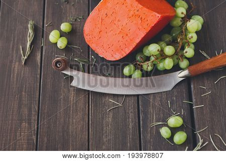 Cheese background. Still life with red gouda pesto, white grapes, herbs and two-handed knife. Copy space, background