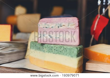 Colored layers of cheese closeup. Gouda pesto cheese with green, white and yellow layers, pink soft cheese with layers of roquefort at grocery shop background